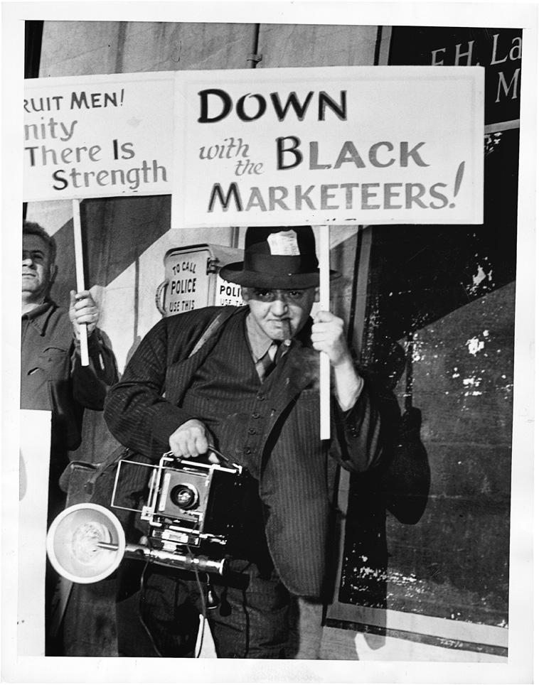 Weegee Lends a Helping Hand, 29. Mai 1945. Weegee auf einer Demonstration gegen den Schwarzmarkt.